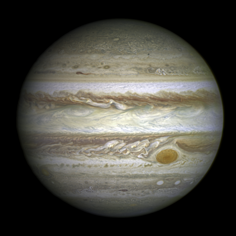 A photograph of Jupiter with vortices around the Great Red Spot in the bottom-right corner.