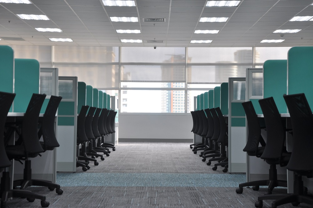 A photograph of an office with two rows of turquoise-colored cubicles and empty black office chairs.