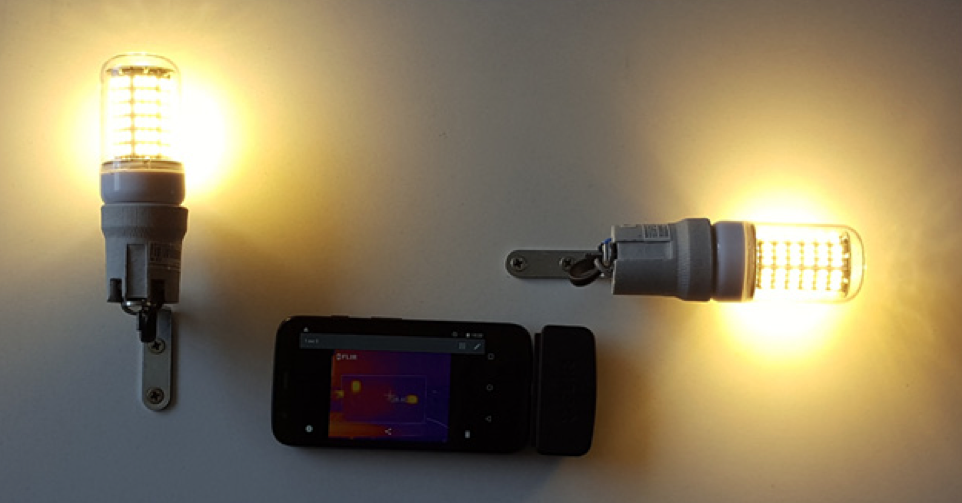 A photograph of the experimental setup for verifying the LED bulb model, with two LED bulbs turned on and an infrared camera in the center.