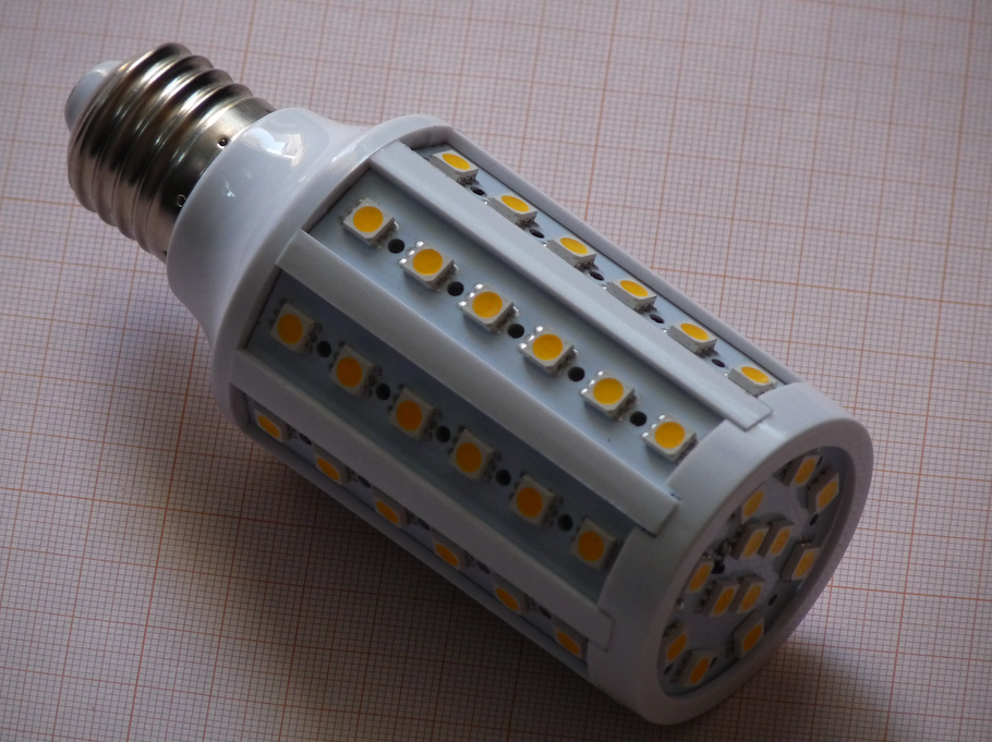 A photograph of a white LED corn bulb with yellow LED chips, resting on a piece of gridded paper.