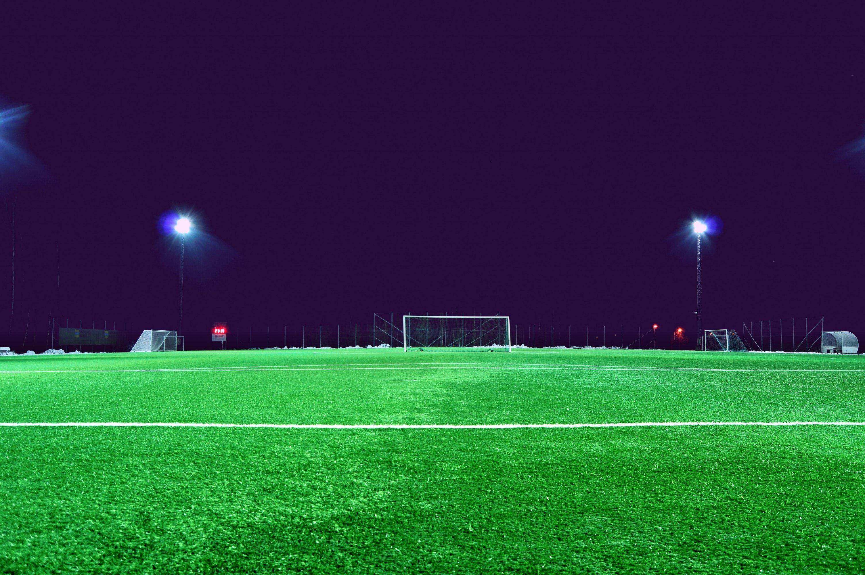 A photograph of a green soccer field at night, with a dark sky and two tall LED lights on either side of the goal post.