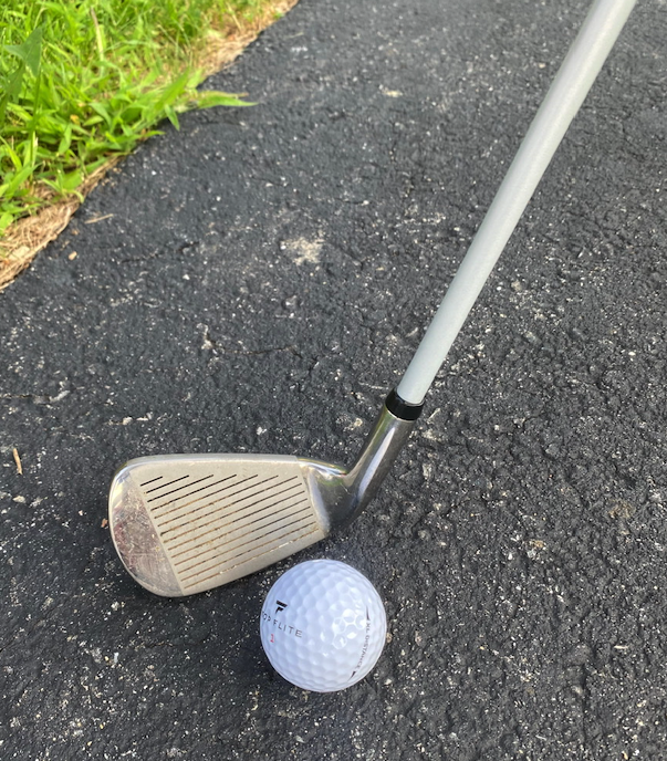 A photograph of a small golf club and golf ball on a concrete surface.