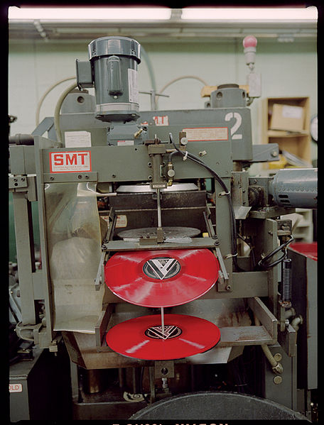 A photograph of a hydraulic press as it manufactures vinyl records in red.